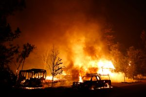 A car burns in front of a burning home. An estimated 13,000 people have had to evacuate because of the Valley Fire.