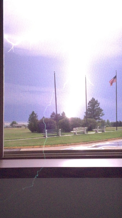 One of the lightning strikes during my North Dakota stay this week. It was totally dark, yet now it is almost like daytime, the flag flying proudly during the storm.